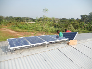 """Foto der Greenpeace Umwelstiftung zur """"Klima-Karawane"""". Solarpanele auf einem Wellblechdach. Im Hintergrund Wald (c) Solafrica"""
