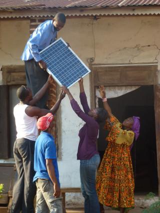 """1 Mann steht erhöht und reicht vier Personen eine Solarpanele. Projekt: """"Klimakarawane"""" (c) Solafrica"""